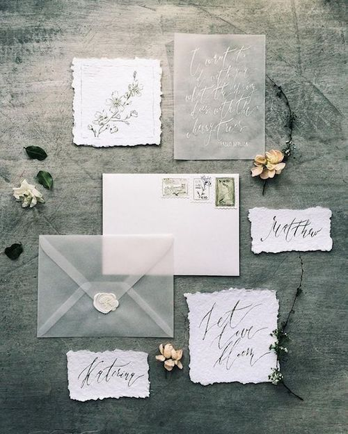 Eclectic hand lettered gray invitation suite with vellum envelopes. Paper with rough edges and a white wax seal.