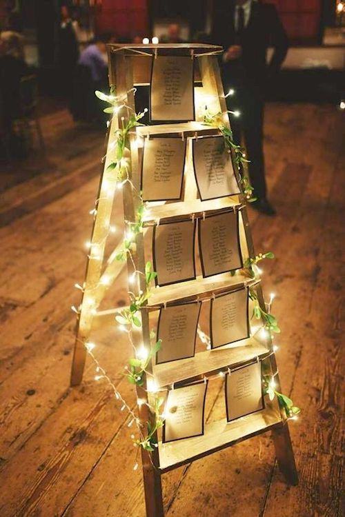 Draw attention to your ladder wedding table plan with ivy wrapped around xmas lights.