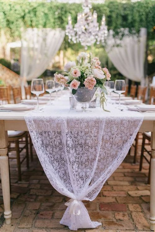 Long white lace table runners add a classy and delicate touch to your garden wedding table decor.