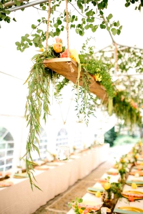 Take advantage of the tent's structure and add some overhead hanging flowers at your wedding reception.