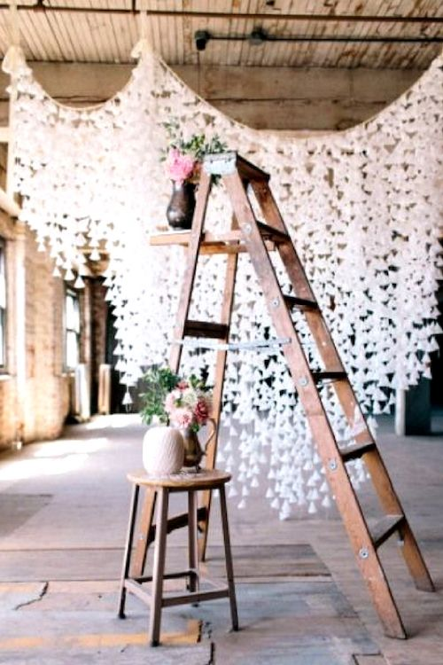 For a more tridimensional photo booth backdrop add a wooden ladder, a small table and flowers on vases. Image by Allie Rae Photography.