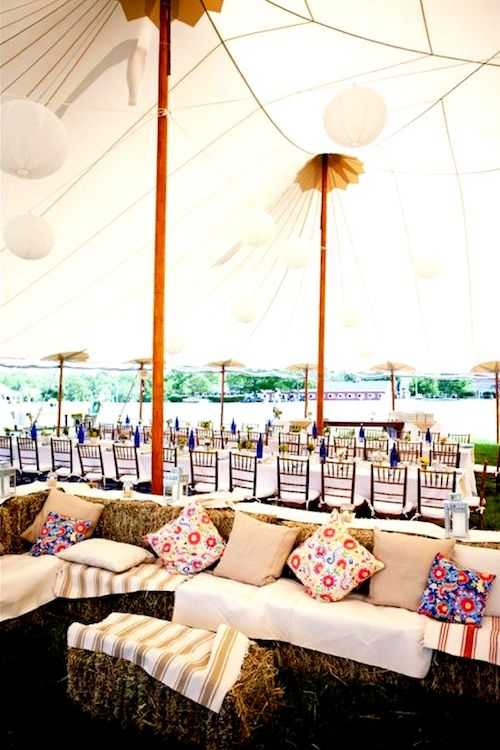 Rustic chic sailcloth pole tent with hay bales as lounge furniture.