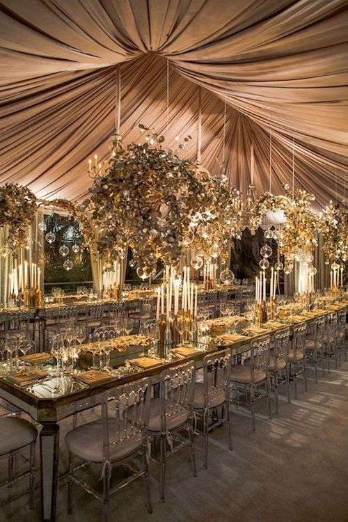 Forget the wedding venue and create your very own and freakiest of spaces! Wedding tent decor with two long tables, hanging greenery, floating glass and chandeliers. Love the crystal-like surface of the tables.