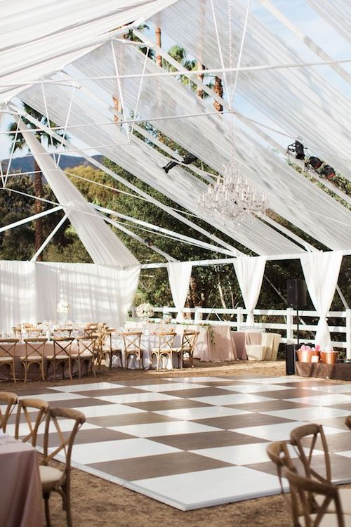 A wedding in the mountains on a sunny day featured a tented decor with open fabric panels. Ojai, California.