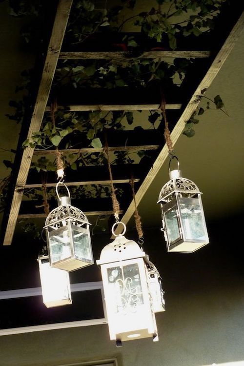 Rustic vintage hanging ladder with lanterns strung with jute.