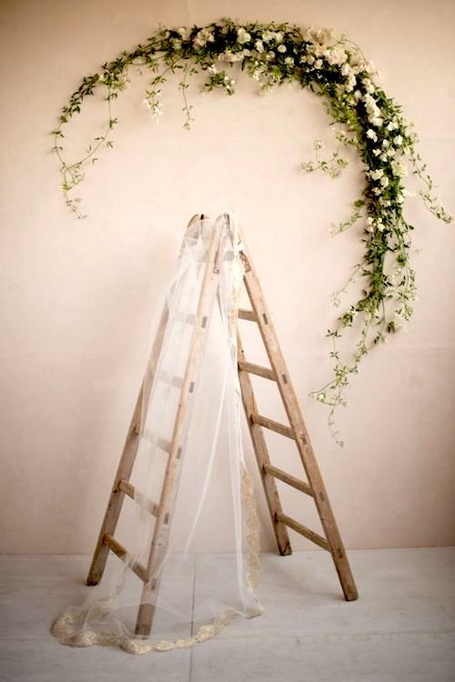 Use a vintage ladder as wedding decor and as the place to hang your wedding veil. Love the oversized greenery wreath.