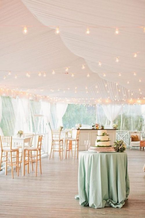 Wedding tent decor in white with string lights that spell luxury. A pale mint table linen ties in the nature that surrounds you.
