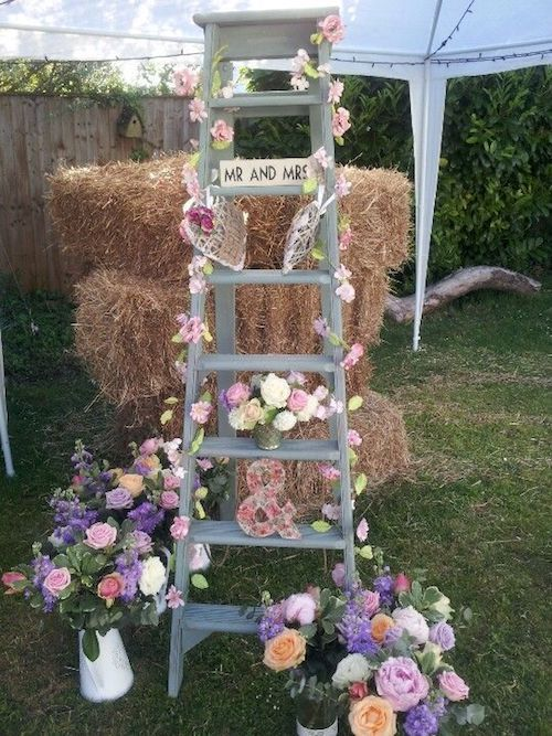 Old wooden ladder decorating ideas for a backyard tented reception. Roses and a few lovey-dovey knick-knacks decorate this gray folding ladder.