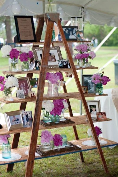 Frames and peonies on this old wooden ladder wedding decor. Tented garden reception.