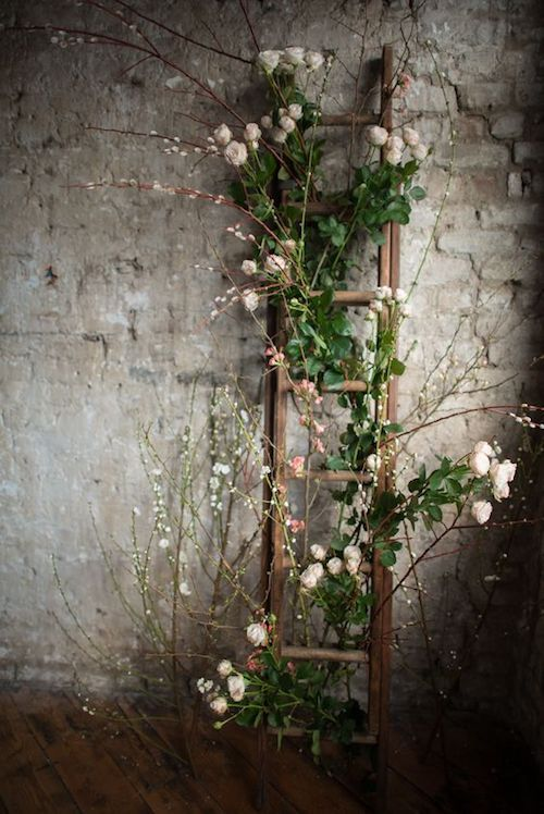 Love this flower entwined leaning rustic wooden ladder wedding decor for an industrial venue. Photo: Shanna Melville Bridal.
