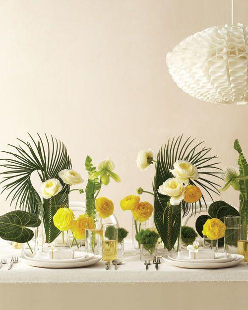 Hojas de palmera rizadas, rosas, ranünculos, orquídeas y una sola espiga de Asplenium crean un arreglo veraniego inspirado en las flores tropicales.