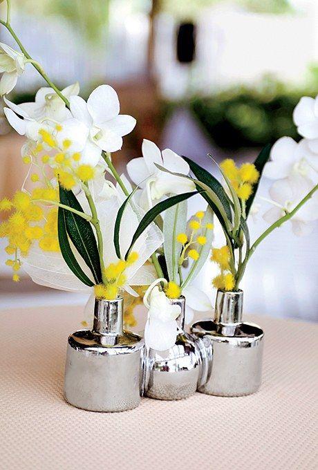 Si organizas una boda destino en la playa, inspírate en estos centros de mesa en vasijas de cromo con orquídeas de seda. Foto: Angie Silvy.