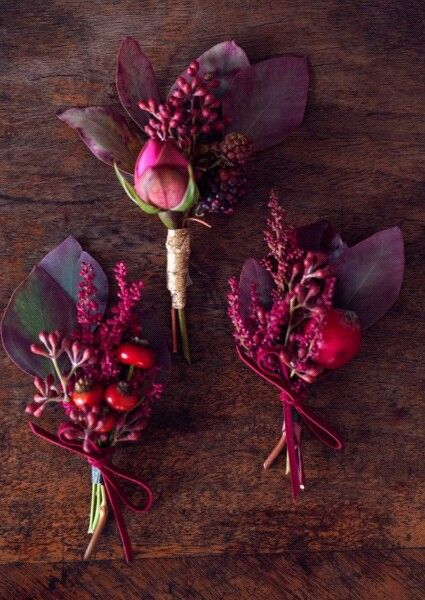 Woodland-inspired burgundy boutonnieres for winter weddings.