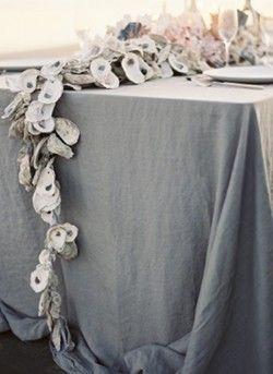 En lugar de centro de mesa un camino de ostras sobre un mantel en gris.