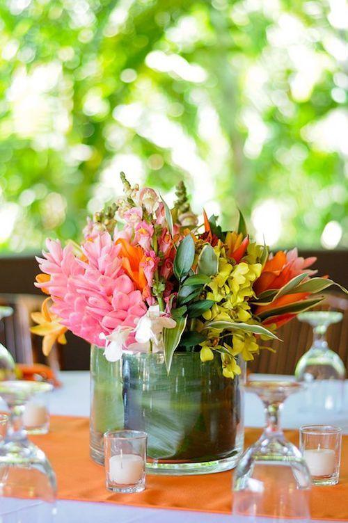 Centros de mesa para playa tropicales. Forra el recipiente con una hoja de banano, agrega agua y un manojo de flores.