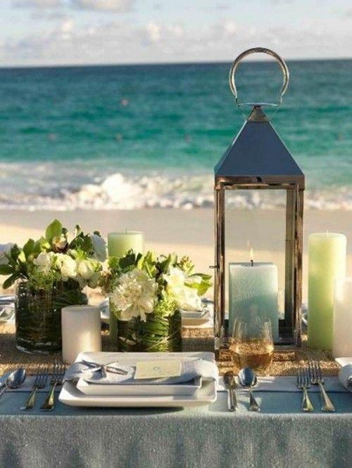 Los faroles serán tus aliados para proteger las velas de la brisa marina en estos centros de mesa para bodas en la playa.