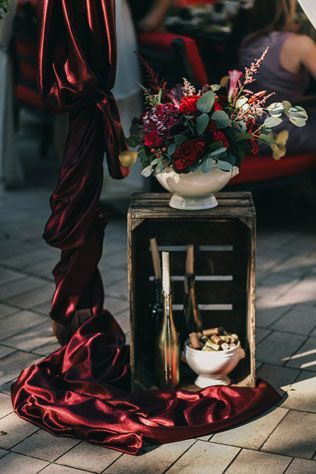 Drapes and flower arrangements in deep burgundy tones.