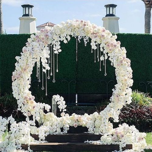 White and blush flower giant wreath with hanging crystals for a glam vibe.