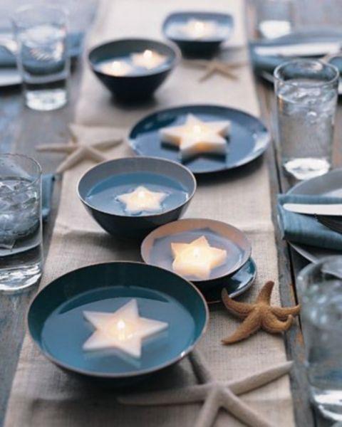 Idea de centros de mesa para bodas en la playa, original y super top. Velas flotantes en platos y tazones rodeadas de estrellas de mar.