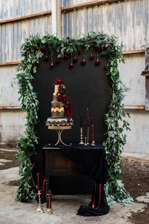 Super original jewel toned cake stand. Finds: vintage desk, blackboard, eucalyptus leaves, black and burgundy candles and gold candelabra. Cake, of course.