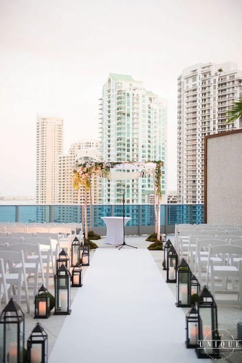 Boda en la azotea del Epic Hotel en Miami, FL. Nos encanta su pasillo bordeado con faroles rústicos y arco de bodas de madera. Foto: Unique.