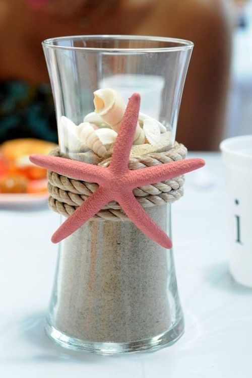 Affordable and original summer centerpieces. Pour sand in a vase, drop some shells on top, decorate with a rope and a pink plastic starfish for a nautical piece.