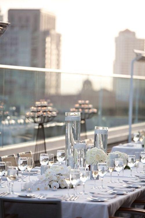 Centros de mesa con velas flotantes, cristales y claveles blancos para una boda perfecta al atardecer en una terraza de la city.