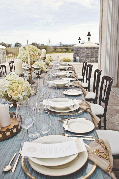 Centros de mesa con flores redondos para una mesa larga con toques de cobre para una recepción inigualable sobre una terraza.