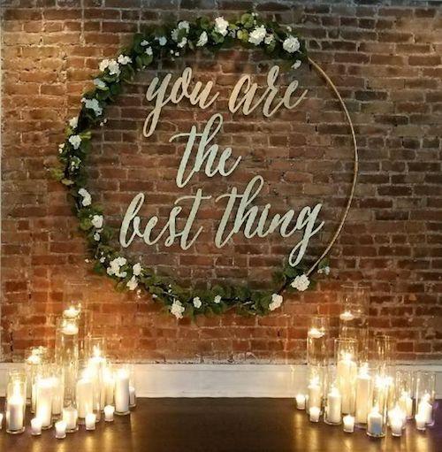 Para la entrada a la recepción o como background para la ceremonia las coronas gigantes impresionarán a tus invitados. Corona de flores gigante con frase de amor.