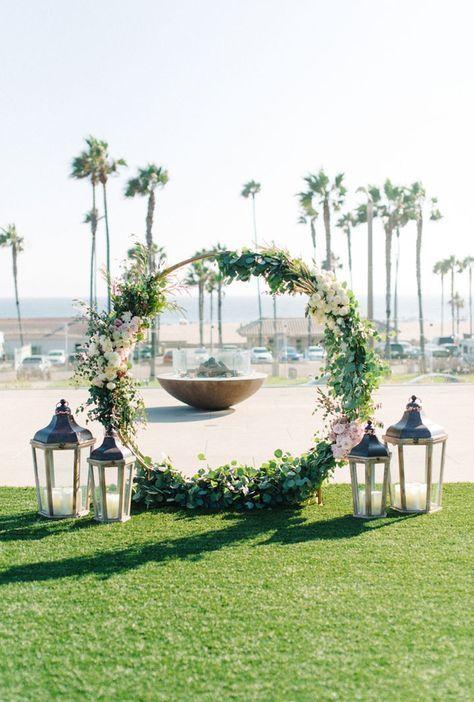 Decora tu ceremonia en la playa con una corona gigante de flores y faroles bien vintage.