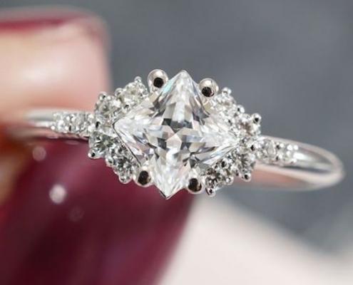 Un diseño de anillo muy original, corte princesa con piedras laterales, detalle de filigrana y pavé.