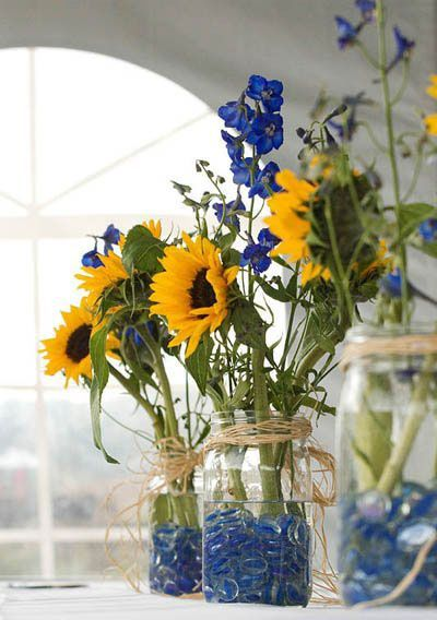 DIY your wedding centerpieces with mason jars, crystals from the dollar store and summery sunflowers.