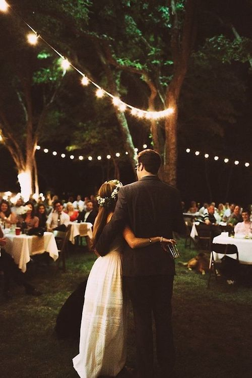 Hanging lightbulb strings adds a charming ambiance to this backyard wedding. Lauren Apel Photo.