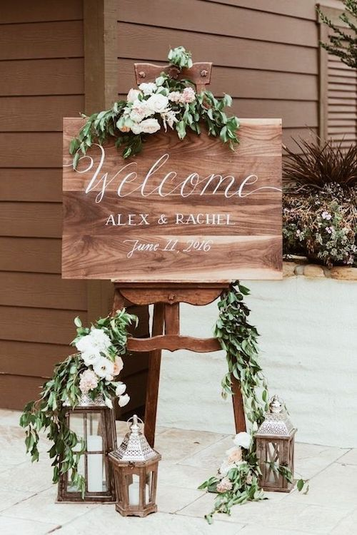 Industrial meets vintage on this ultra romantic welcome wedding sign. Lanterns, flowers and greenery do the trick.