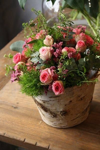 To achieve this look, cover the container with tree bark. Add roses, greenery and moss.