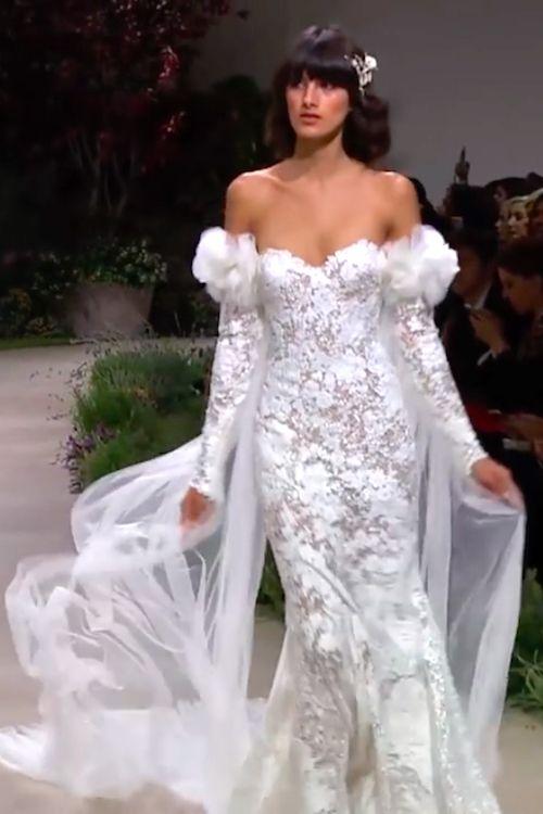 Si tus hombros son soñados, este vestido de Pronovias es para ti. Escote corazón, hombros al descubierto y mangas largas con detalle. Carina.