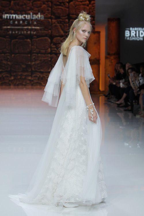 Mangas que se transforman en capa para una novia moderna y angelical. Amamos la creatividad de Inmaculada García. Crédito de fotografía: Barcelona Bridal Fashion Week.