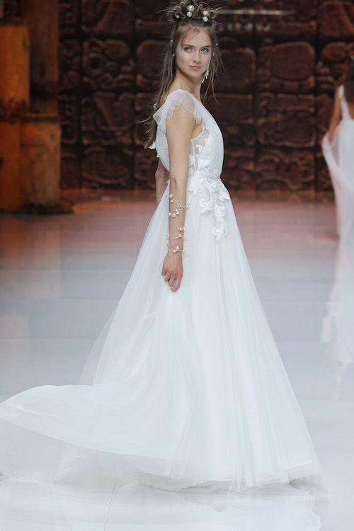 Vestidos de novias de tejidos con texturas inigualables. Divino el detalle de un pendiente largo y uno corto. Inmaculada García 2019.