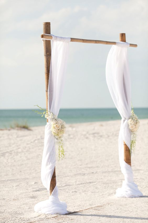 Simple and affordable wedding arch, solidly tied bamboo canes with white rope. Draped fabric and flower bouquets add texture and class to this Clearwater, Florida beach ceremony. Photo: Stephanie A Smith Photography.