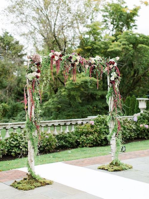 Fairytale-worthy vine and moss draped birchwood arch for an outdoor wedding.
