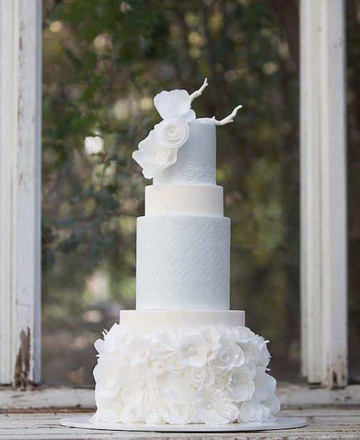 Tarta de bodas blanca de cuatro pisos, redonda y textura con rosas de papel de arroz.
