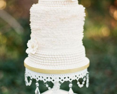 Irresistible delicia vintage en blanco con detalles de encaje sobre un sostén de tarta con caireles.