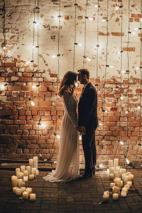 Llenar un espacio de bodas con velas blancas e iluminación colgante da la sensación de algo muy especial. Boda industrial íntima.