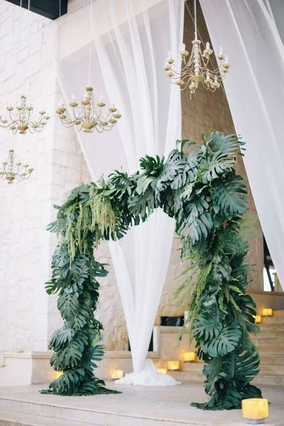 Luxury palm frond floral wedding ceremony arch ideas.
