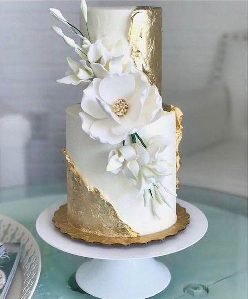 Impresionante pastel blanco y dorado y una magnolia para bodas.