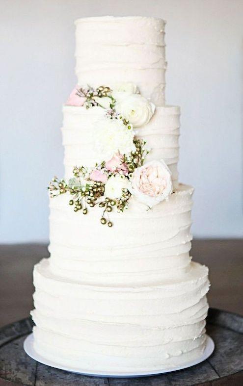 Cake cubierto de crema de mantequilla blanca con detalle de flores.