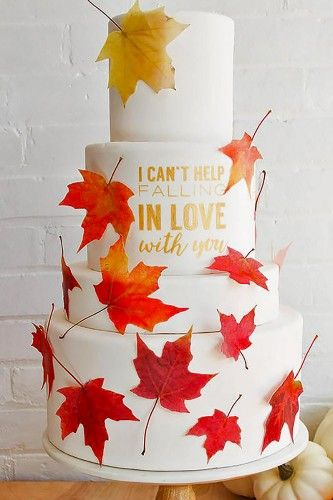 Pastel de boda blanco otoñal decorado con hojas de maple y letras en dorado.