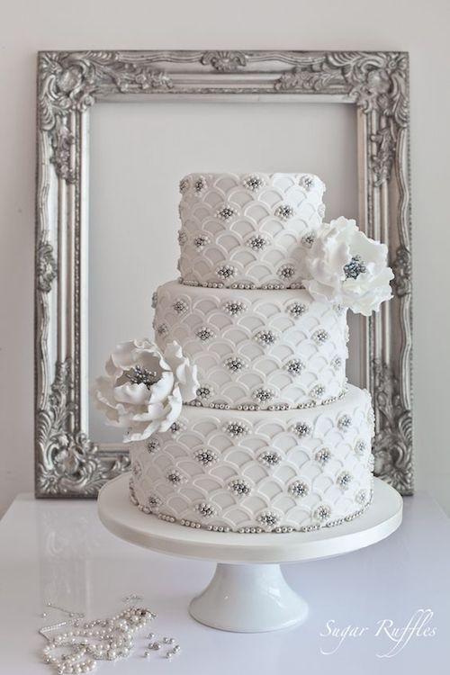 Inmaculado pastel de bodas en blanco y plateado con un festoneado en plata y perlas de Sugar Ruffle.