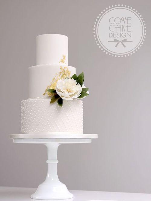 Pastel de fondant blanco con peonias de azúcar forrada con perlas glaseadas y un detalle abstracto en hojuelas doradas de Cove Cake Design.