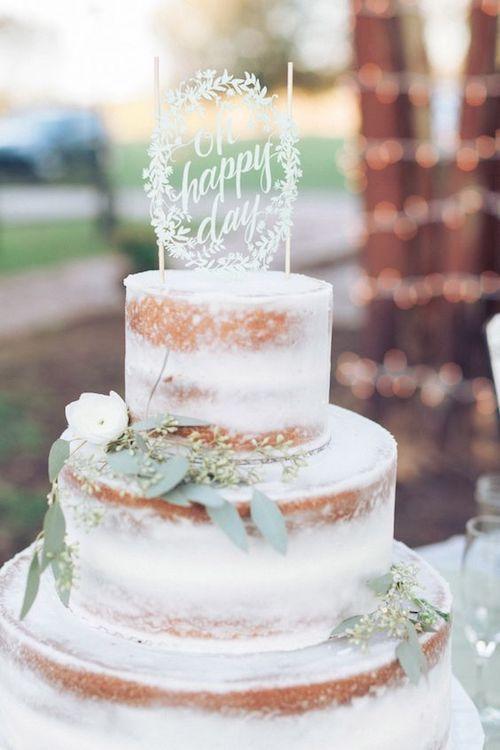 Un pastel semi-desnudo con una ligera capa de buttercream para una boda íntima en el jardín de casa en Lousiana.